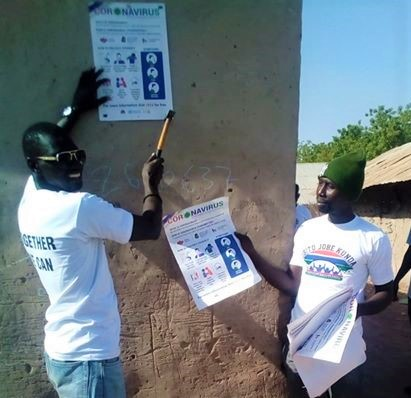 Members of Sibito Jobe Kunda Youth Association putting up COVID-19 posters produced by UNFPA The Gambia in their community